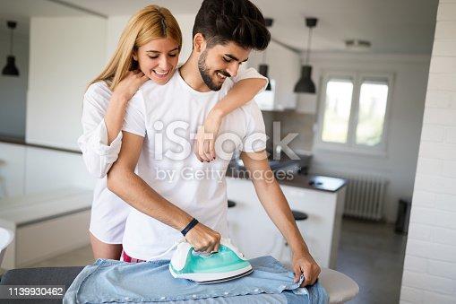 802472024 istock photo Girl bothering boyfriend while ironing shirt 1139930462