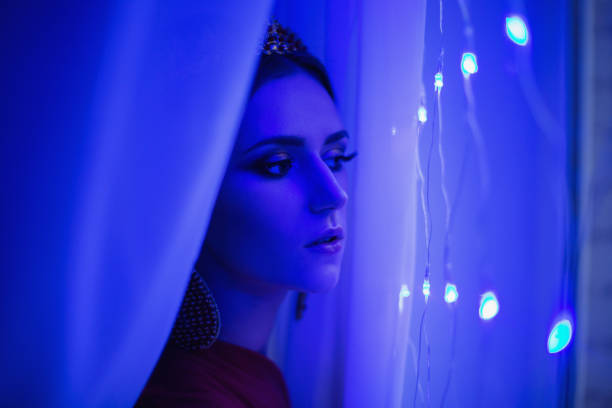 Girl brunette in a red dress with beautiful hairstyle, earrings of beads and a crown on her head and bright makeup. Female style. Mysterious woman. Blue light stock photo