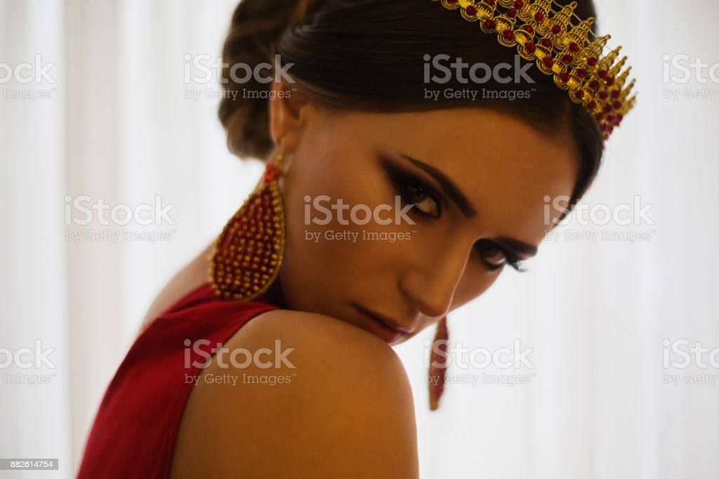 Girl brunette in a red dress with beautiful hairstyle, earrings of beads and a crown on her head and bright makeup. Female style. Mysterious woman. stock photo