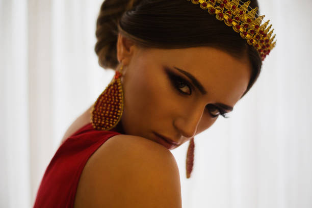 brünette mädchen in einem roten kleid mit schöne frisur, ohrringe mit perlen und eine krone auf ihrem kopf und hellen make-up. weiblichen stil. geheimnisvolle frau. - ägyptisches make up stock-fotos und bilder
