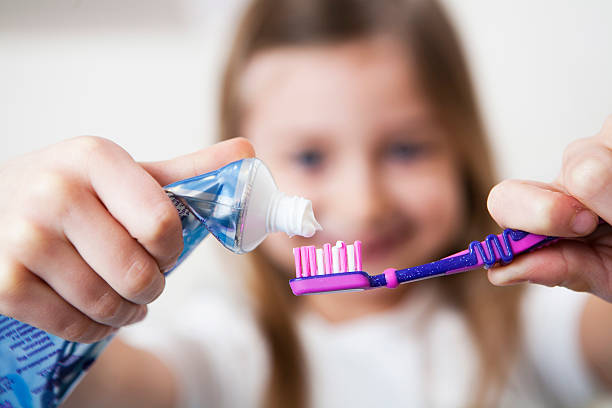 Girl brushing her teeth stock photo