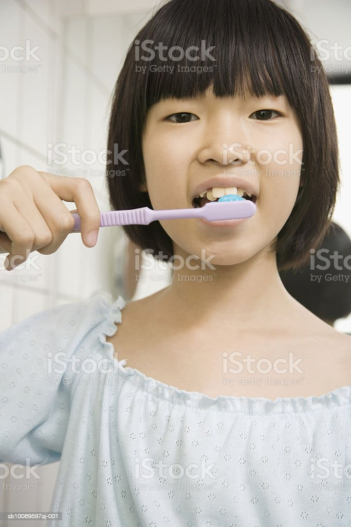 Girl (10-11) brushing teeth, portrait royalty-free stock photo