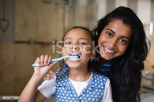istock Girl brushing teeth with mother in bathroom 800577062