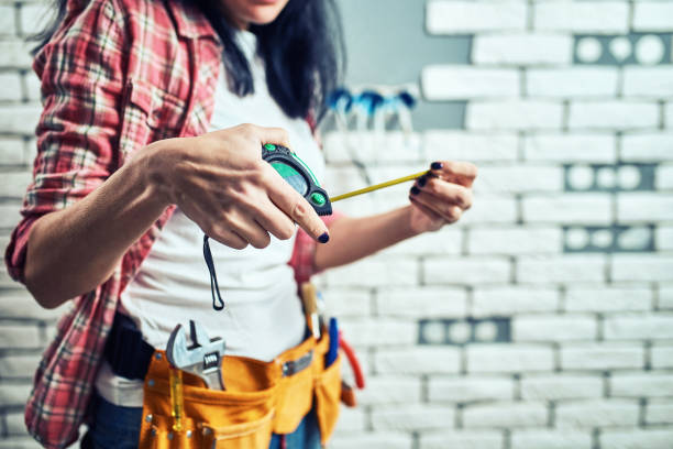 Girl builder in special clothes at the workplace. stock photo