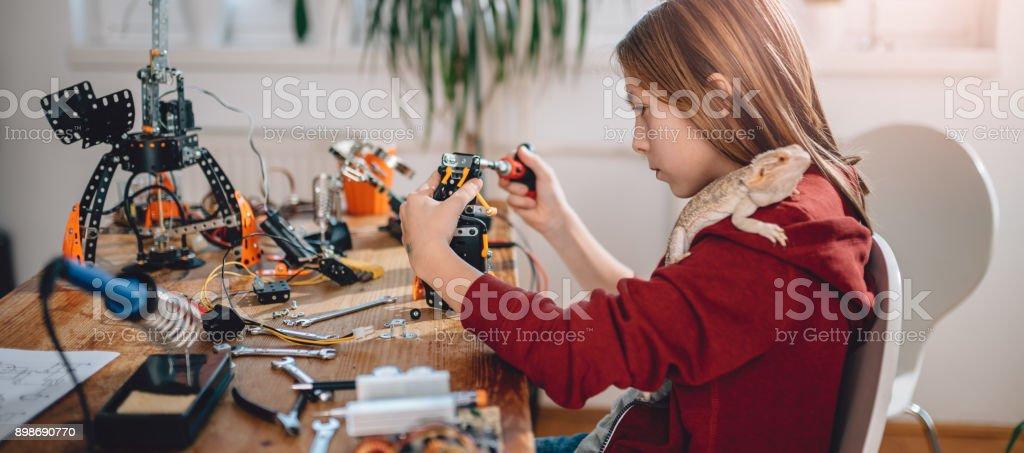 Girl building robot stock photo