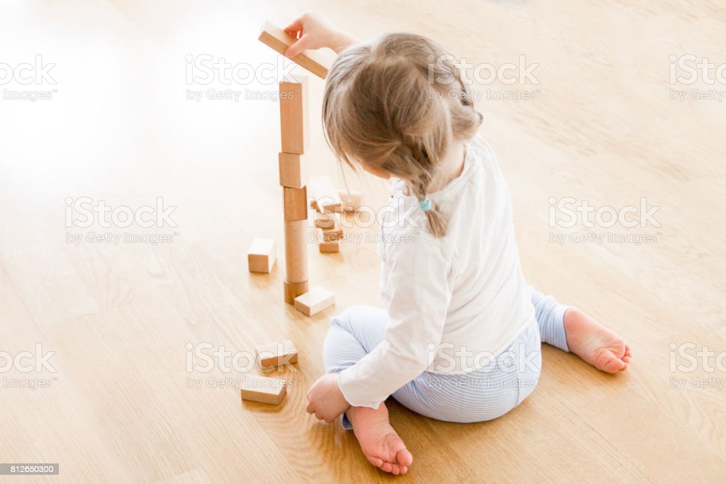 Girl buildning tower of wooden blocks sitting on the floor stock photo
