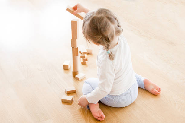 girl buildning tower of wooden blocks sitting on the floor - torre struttura edile foto e immagini stock