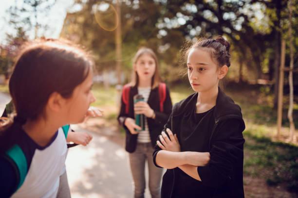 girl bullying girl at schoolyard - persona in secondo piano foto e immagini stock