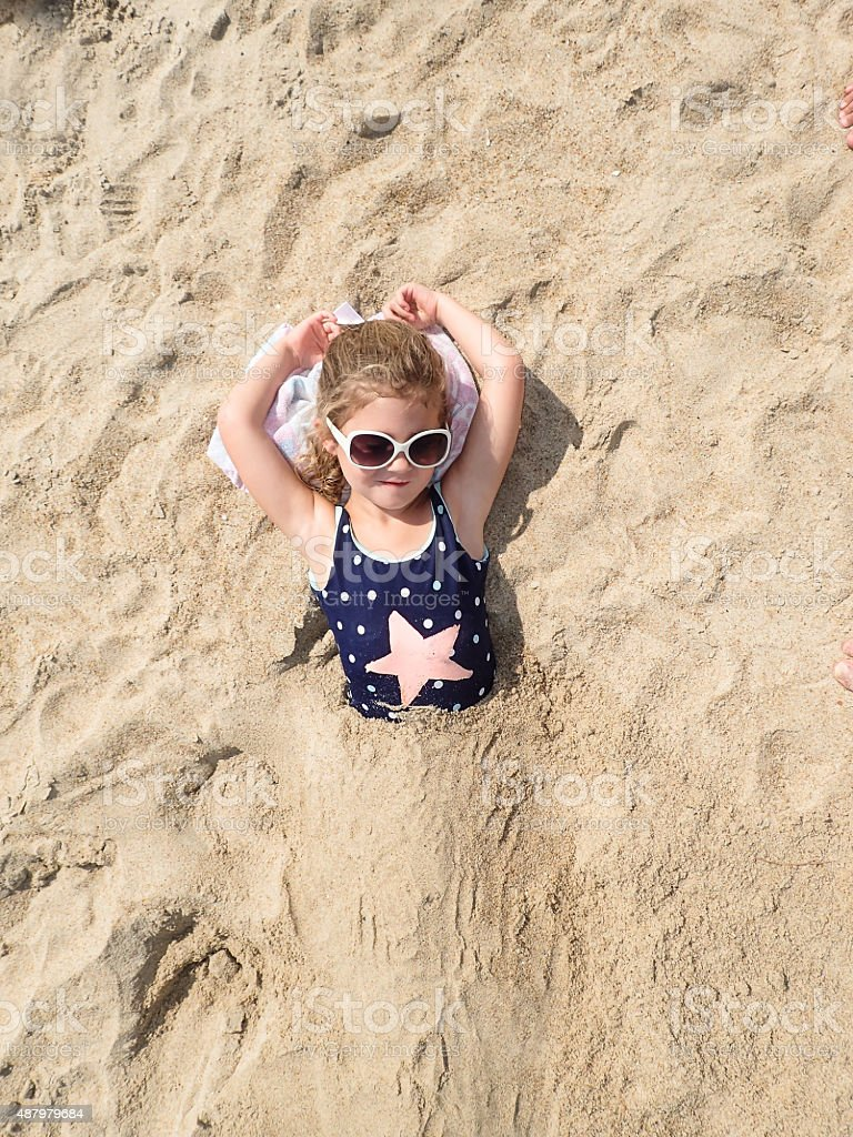 Girl buried in sand stock photo