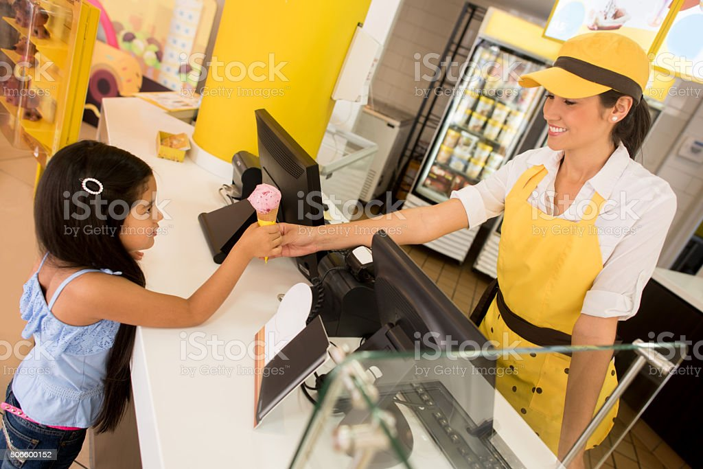 Girl buying an ice cream at a shop stock photo