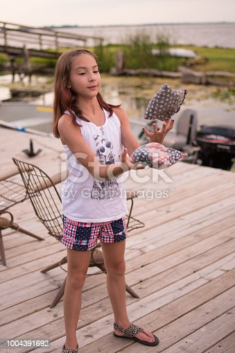 Girl with white shirt and red, white, and blue shorts, and braid in her hair and earrings juggling bean bags
