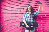 Girl by pink brick wall with skateboard