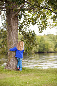 """Young girl """"hugging"""" a tree while looking out at the river."""