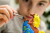 Girl Carefully Painting A Piece Of Horse Pottery Made Of Clay