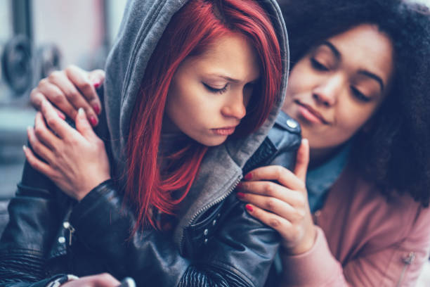 Girl caring about depressed friend stock photo
