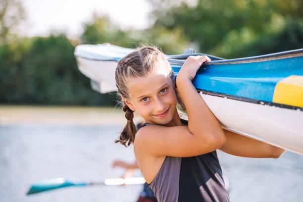 Girl carries a kayak stock photo