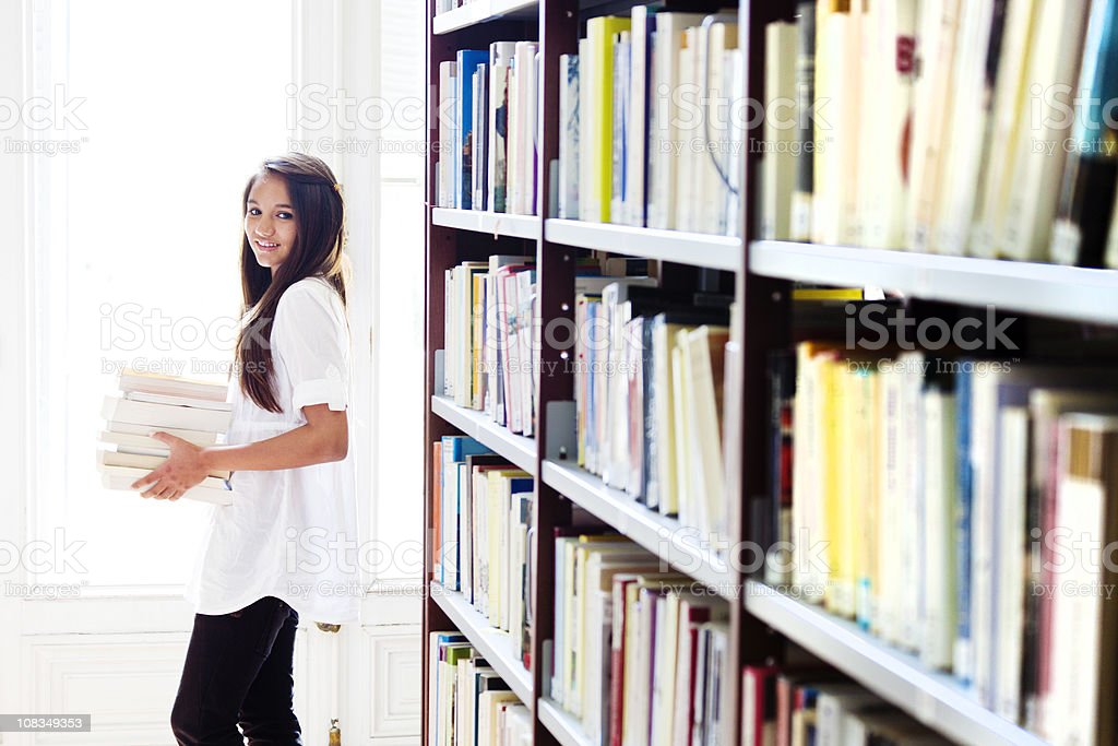 girl carrying books in library royalty-free stock photo