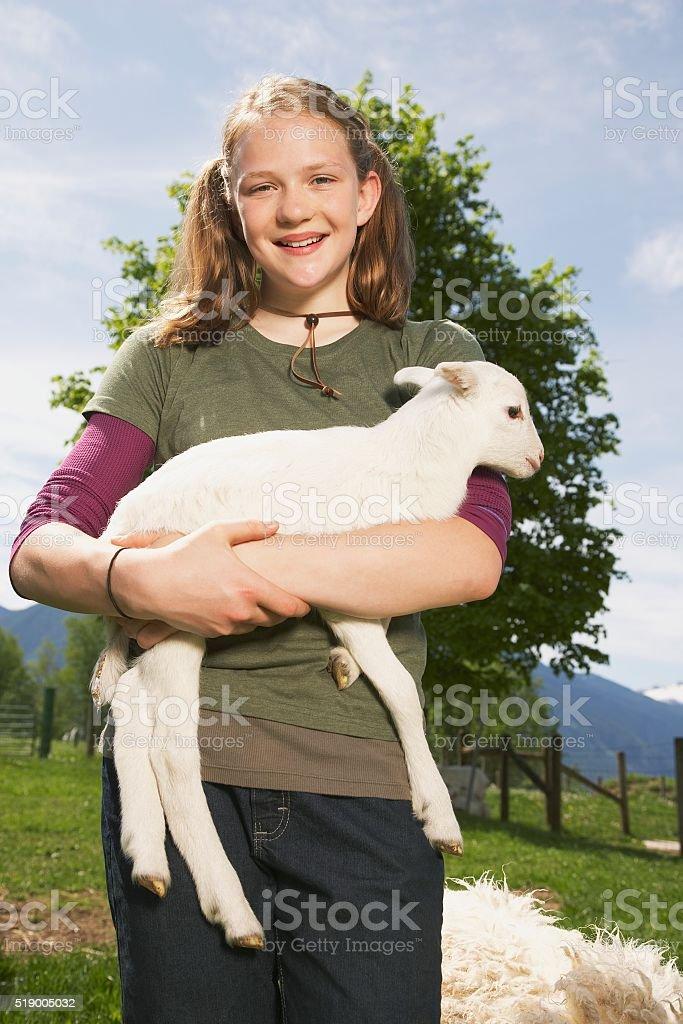 Girl carrying lamb on farm stock photo