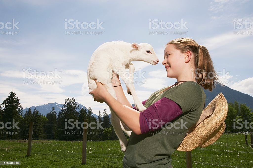Girl carrying lamb stock photo