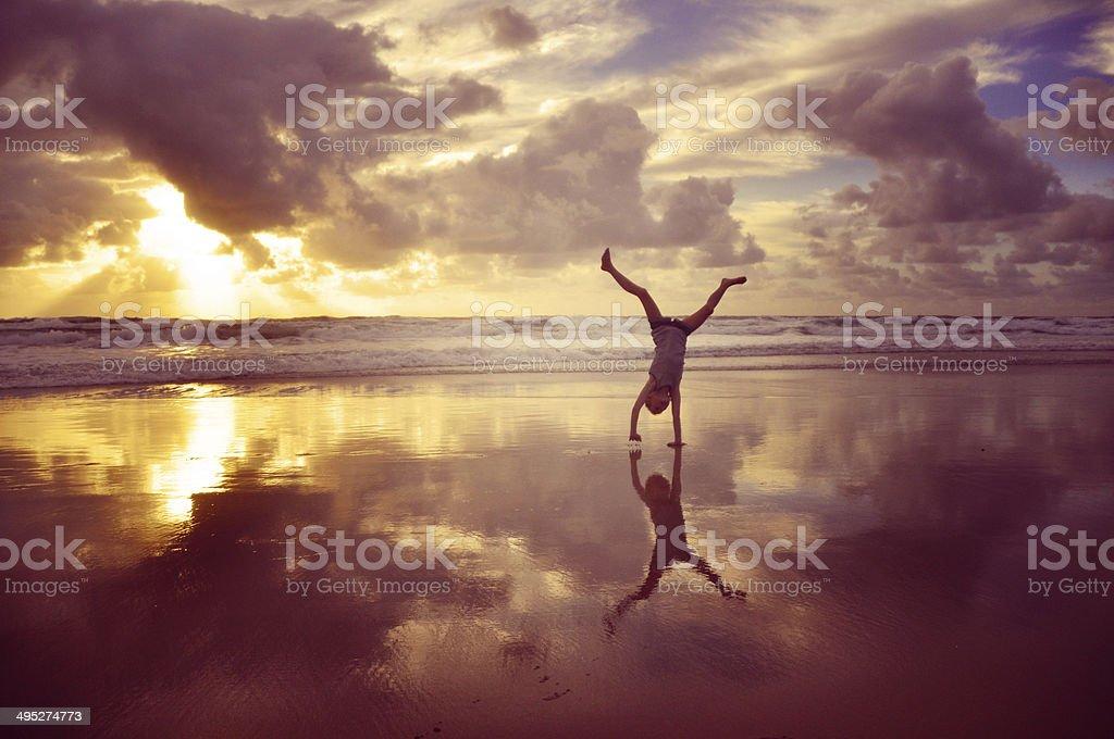 Girl cartwheeling at beach stock photo