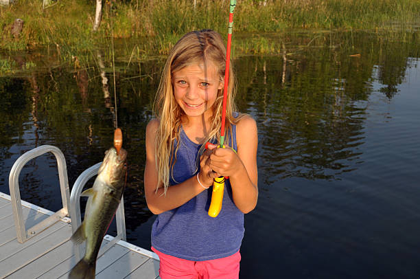 Girl Catches Fish on a Lake stock photo