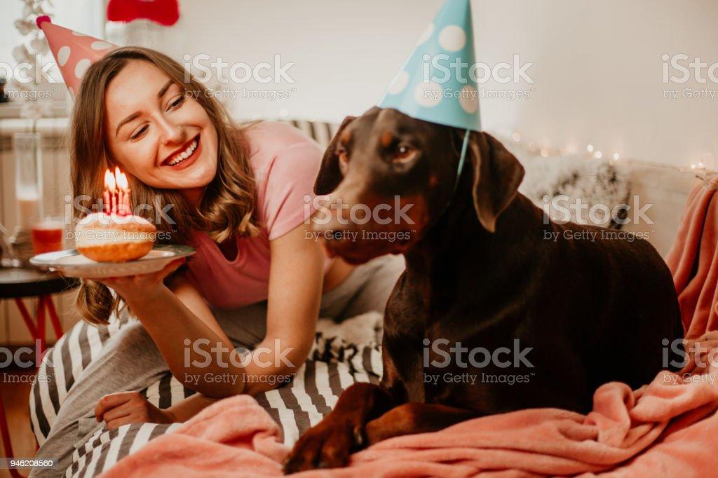 Beautiful young girl celebrating her doberman male dog\'s birthday...
