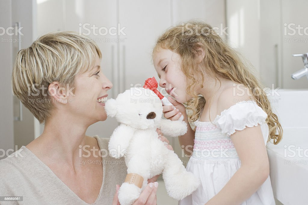 Girl checking stuffed animals ear with otoscope royalty-free stock photo