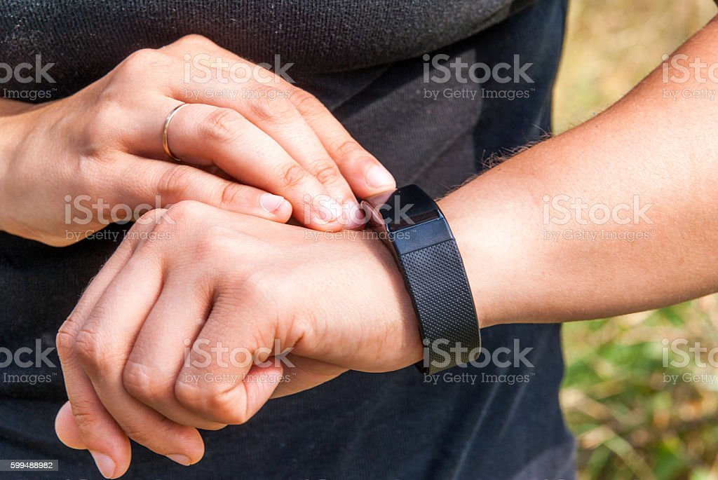 Girl checks the information on the screen of the fitness band stock photo