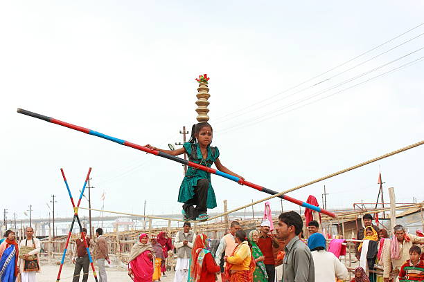 Girl child doing circus play to earn money Allahabad, India - February 24, 2013: A child girl crosses a rope at 20 feet height during Kumbh mela in Allahabad, India. illiteracy stock pictures, royalty-free photos & images