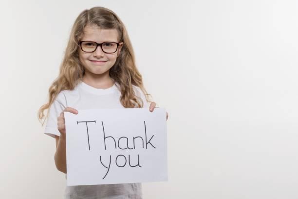 Fillette tenant le morceau de papier avec un mot Merci. Backgrounde blanc - Photo