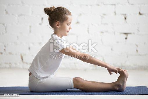 istock Girl child in paschimottanasana pose, white studio background 639589586
