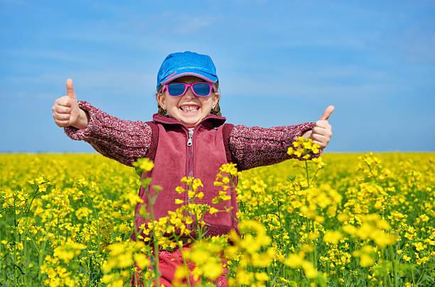 Chica niño en campo de colza con flores amarillo brillante - foto de stock