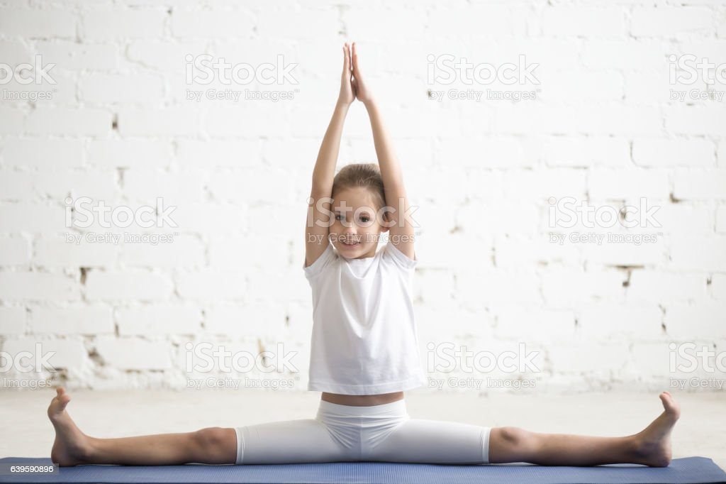 Girl child in Samakonasana pose, white studio background stock photo