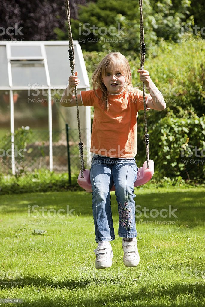 Girl child on swing in the garden royalty-free stock photo