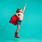 Adorable girl in red superhero costume and mask jumping with a arm raised. Girl in red cape, gumboot and mask fantasizing that she is superhero over blue background.
