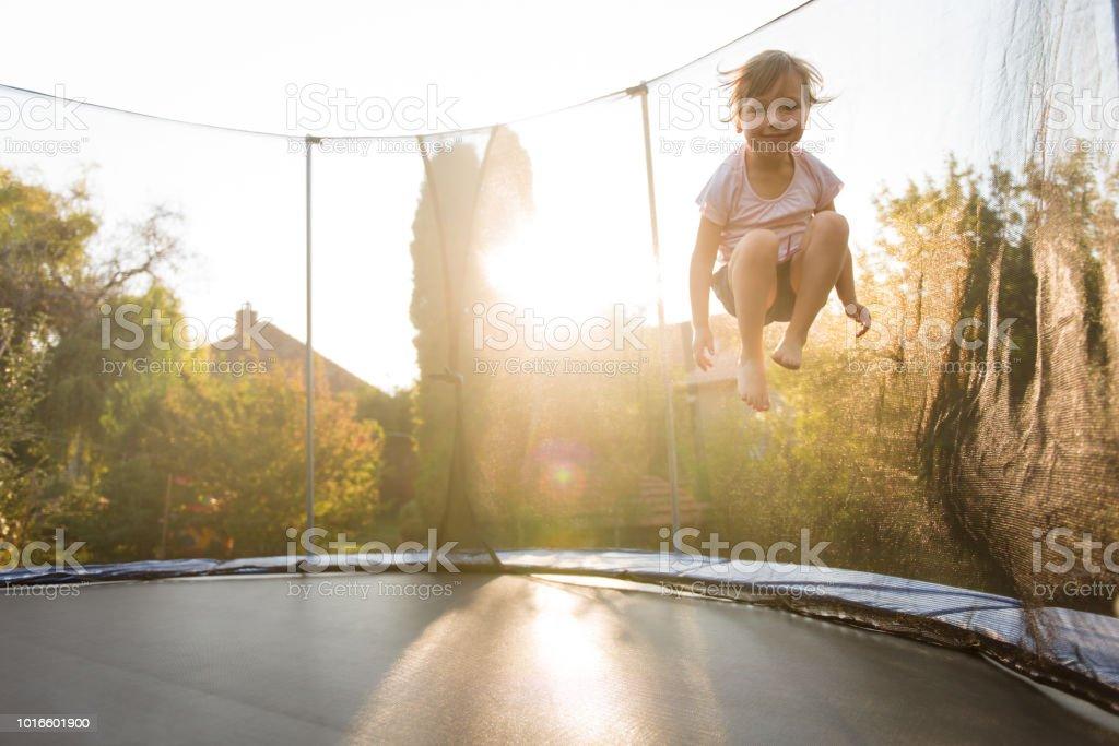 Girl child playing on trampoline in backyard
