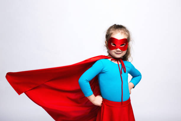 Girl child plays in a superhero red cloak in the wind. stock photo