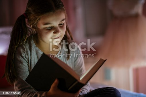 Girl child reads book in bed. Shadow DOF. Developed from RAW; retouched with special care and attention; Small amount of grain added for best final impression. 16 bit Adobe RGB color profile.