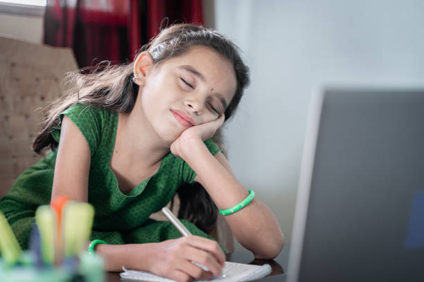 girl child sleeping during online class in front of laptop - concept of tired kid from distance learning or online education at home during covid-19 or coronavirus lockdown. - young girl computer home front imagens e fotografias de stock