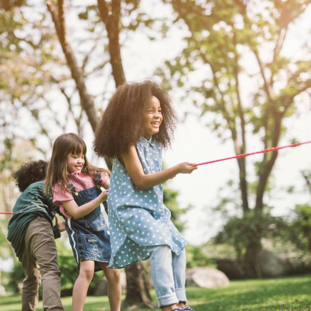 mädchenkinder spielen tauziehen im park - sommerfest kindergarten stock-fotos und bilder