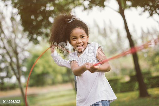 Girl children playing tug of war at the park