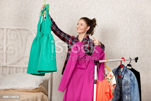 Smiling girl holds two dresses while choosing clothes