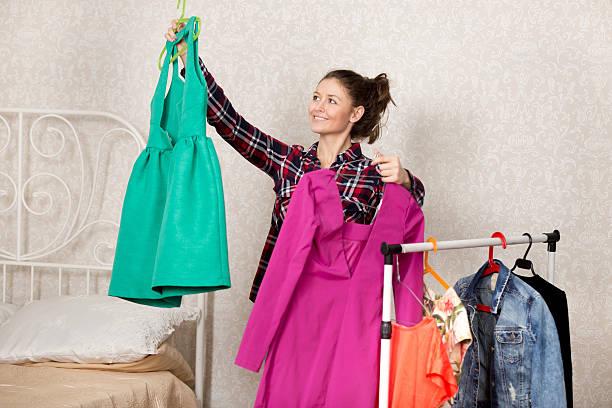 mädchen wählt kleider - lila, grün, schlafzimmer stock-fotos und bilder