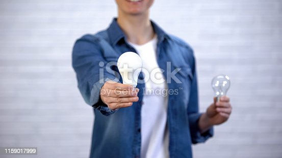 Girl chooses energy saving led bulb instead of incandescent lamp, efficiency