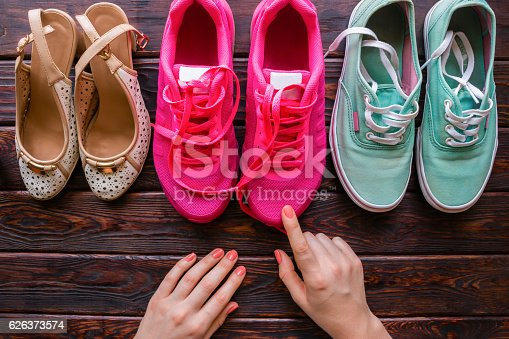 917262406istockphoto girl chooses shoes on a wooden background 626373574
