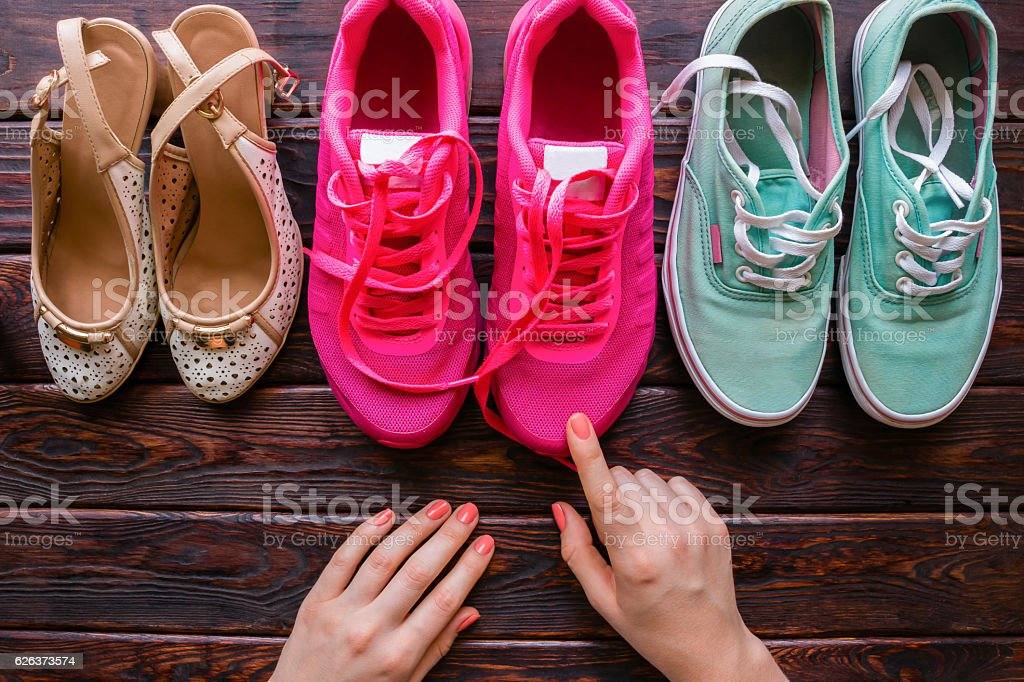 girl chooses shoes on a wooden background stock photo