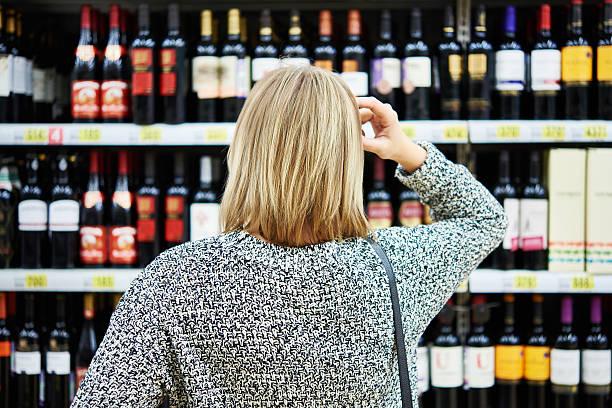 ragazza sceglie il vino - 2015 foto e immagini stock