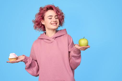 Girl choosing between junk and healthy food