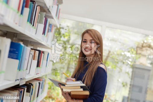 istock girl choosing book in library and smiling 114305994