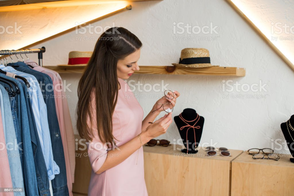 girl choosing glasses in boutique royalty-free stock photo